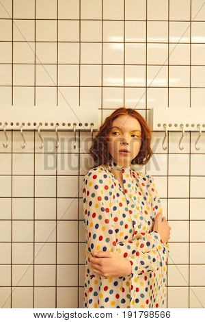 Fashion portrait of serious young redhead curly lady standing in cafe. Looking aside.