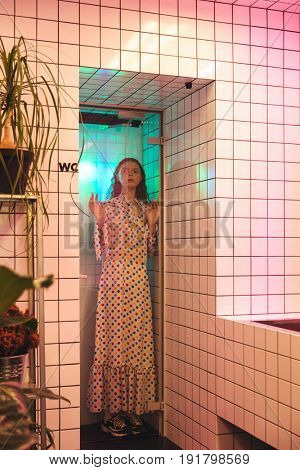 Fashion portrait of young redhead curly lady standing in cafe at latrine at shower. Looking aside.