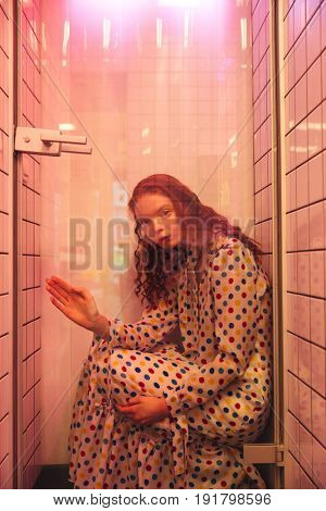 Fashion portrait of young redhead curly woman in cafe at latrine at shower. Looking at camera.