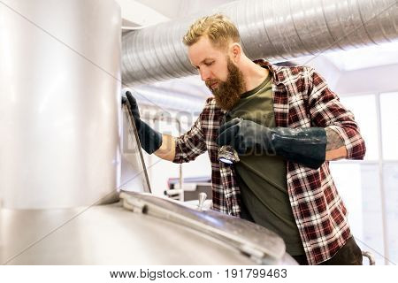 manufacture, business and people concept - man with flashlight working at craft brewery or beer plant