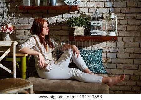 Daydreaming ginger-haired woman relaxing at home. Side view.