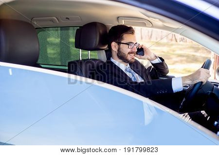 Businesswoman talking on the phone while driving a comfortable car