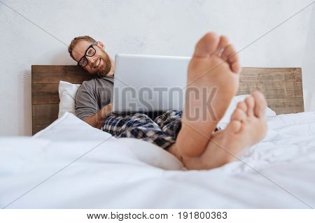 Working weekends. Happy young man lying in bed with a laptop on his stomach and grinning broadly while looking into the camera.