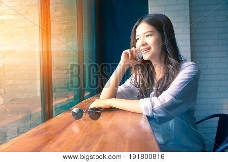 young happy asian woman using and talking on her phone at a cafe with warm light coming in from the window duo tone colors warm high light and cool blue shadow