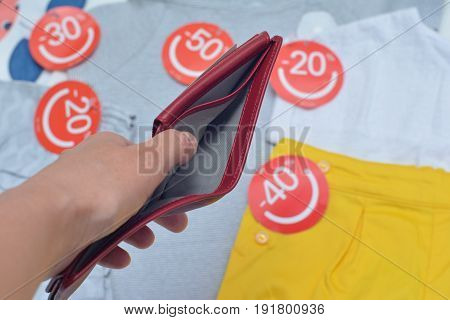 Female hands holding empty red purse background with lothes with discount labels