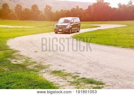 Car on dirt road curve and green grass park
