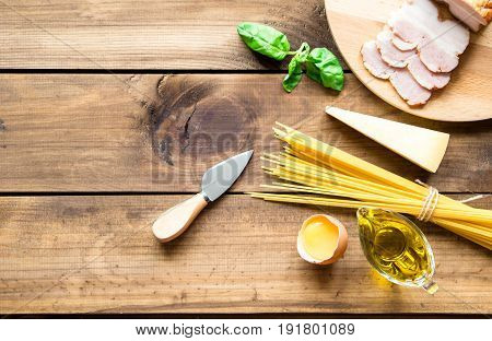 Italian carbonara ingredients on dark wooden background. space for text