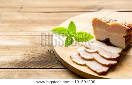 Raw smoked bacon slices on wooden board which herbs on dark wooden background