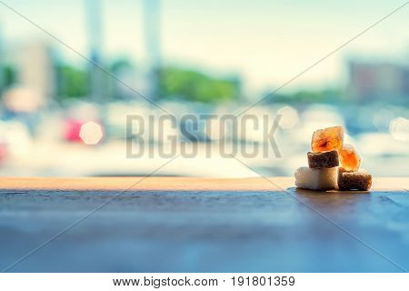 Close up several lumps of sugar lie on wooden table outdoors with blurred background
