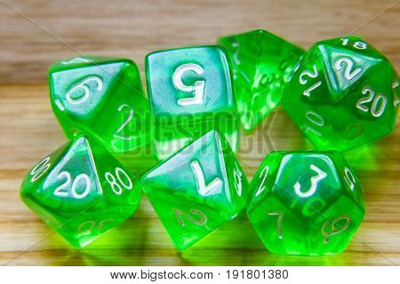 A Lot Of Translucent Green Playing Dice On A Wooden Background With Numbers On Top
