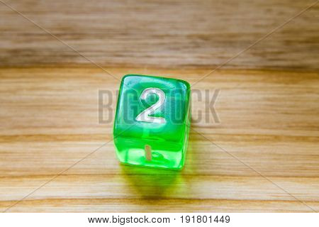 A Translucent Green Six Sided Playing Dice On A Wooden Background With Number Two On A Top