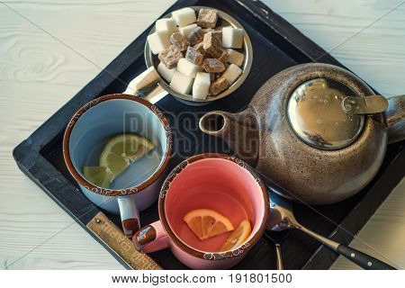 Close up vintage tea set with blue and pink metal mugs, kettle, sugar-tongs and lumps of sugar on wooden tray