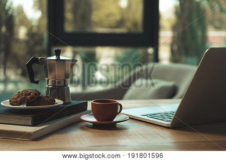 Close-up View Of Laptop, Cup Of Coffee, Moka Pot And Chocolate Chip Cookies With Books On Wooden Tab