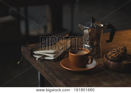 Close-up View Of Notebook With Pencil, Cup Of Coffee, Moka Pot And Chocolate Chip Cookies On Wooden