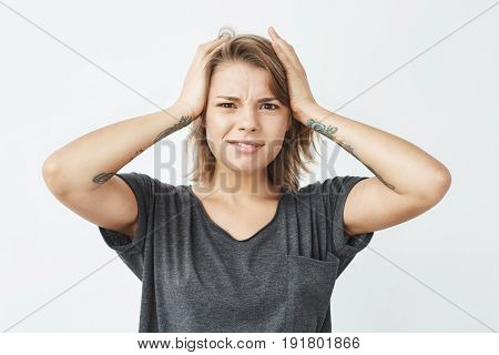 Displeased young pretty girl looking at camera ashamed holding head over white background. Copy space.