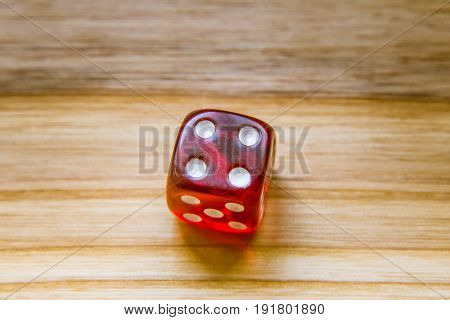 A Translucent Red Six Sided Playing Dice On A Wooden Background With Number Four On A Top