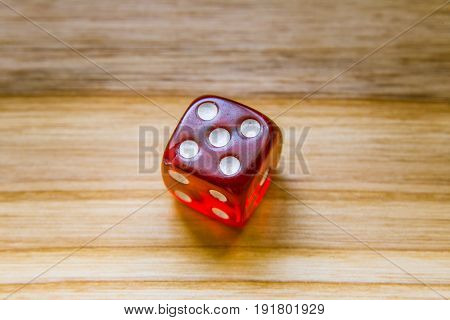 A Translucent Red Six Sided Playing Dice On A Wooden Background With Number Five On A Top