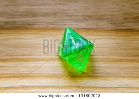 A Translucent Green Eight Sided Playing Dice On A Wooden Background With Number One On A Top