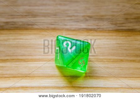 A Translucent Green Eight Sided Playing Dice On A Wooden Background With Number Two On A Top