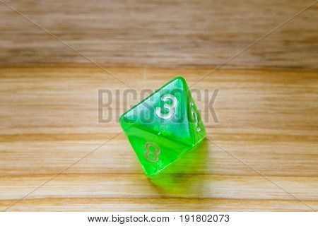 A Translucent Green Eight Sided Playing Dice On A Wooden Background With Number Three On A Top