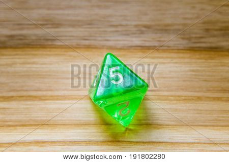 A Translucent Green Eight Sided Playing Dice On A Wooden Background With Number Five On A Top