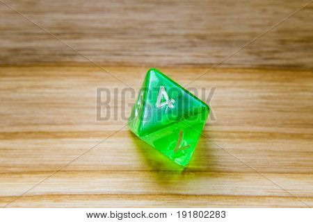 A Translucent Green Eight Sided Playing Dice On A Wooden Background With Number Four On A Top