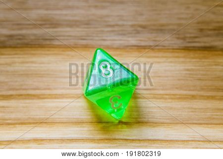 A Translucent Green Eight Sided Playing Dice On A Wooden Background With Number Eight On A Top