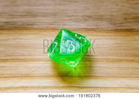 A Translucent Green Ten Sided Playing Dice On A Wooden Background With Number Three On A Top