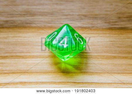 A Translucent Green Ten Sided Playing Dice On A Wooden Background With Number Four On A Top
