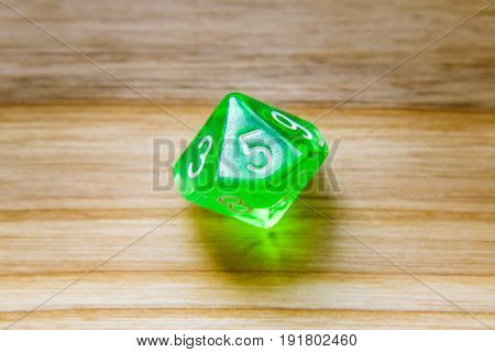 A Translucent Green Ten Sided Playing Dice On A Wooden Background With Number Five On A Top