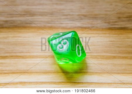 A Translucent Green Ten Sided Playing Dice On A Wooden Background With Number Eight On A Top