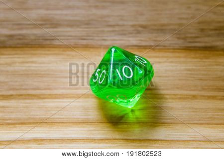 A Translucent Green Ten Sided Playing Dice On A Wooden Background With Number Ten On A Top