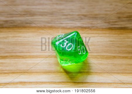 A Translucent Green Ten Sided Playing Dice On A Wooden Background With Number Thirty On A Top