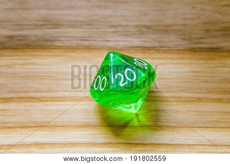 A Translucent Green Ten Sided Playing Dice On A Wooden Background With Number Twenty On A Top