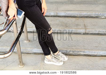 Woman's long legs in black jeans pants on a stone stairs