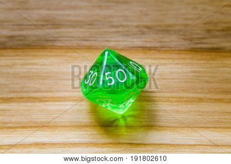 A Translucent Green Ten Sided Playing Dice On A Wooden Background With Number Fifty On A Top
