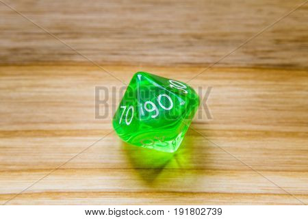 A Translucent Green Ten Sided Playing Dice On A Wooden Background With Number Ninety On A Top
