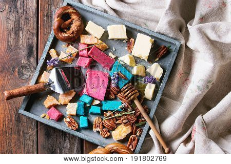 Variety of colorful holland cheese traditional soft, old, pink basil, blue lavender served with pecan nuts, honey, lavender flowers, pretzels bread on tray over wooden planks background. Flat lay