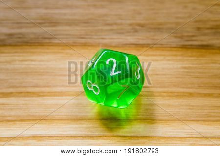A Translucent Green Twelve Sided Playing Dice On A Wooden Background With Number Two On A Top