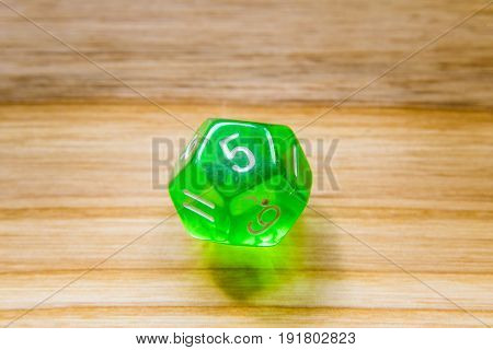 A Translucent Green Twelve Sided Playing Dice On A Wooden Background With Number Five On A Top