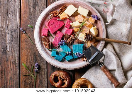 Variety of colorful holland cheese traditional soft, old, pink basil, blue lavender served with pecan nuts, honey, lavender flowers, pretzels bread on plate over wooden planks background. Flat lay