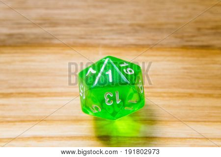 A Translucent Green Twenty Sided Playing Dice On A Wooden Background With Number One On A Top