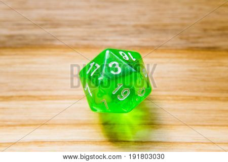 A Translucent Green Twenty Sided Playing Dice On A Wooden Background With Number Three On A Top