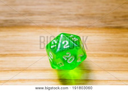 A Translucent Green Twenty Sided Playing Dice On A Wooden Background With Number Two On A Top