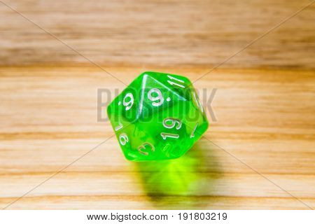 A Translucent Green Twenty Sided Playing Dice On A Wooden Background With Number Nine On A Top