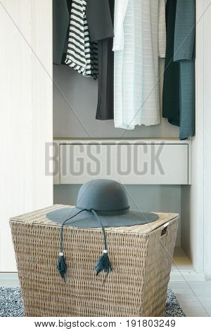 Black Hat On Basket With Cloths Hanging In Closet In Background