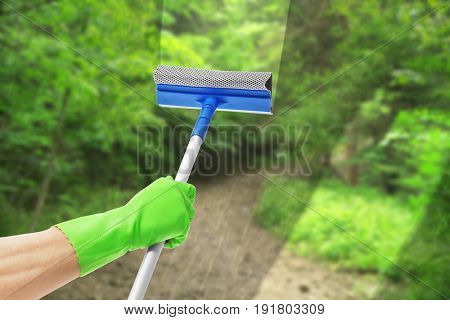 Man removing dirt from glass with squeegee. View of landscape through window. Cleaning service concept