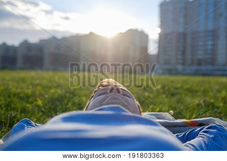 Happy caucasian man lying on the green grass with arms outstretched. City on background view