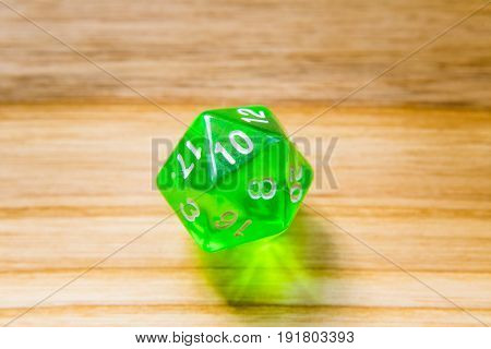 A Translucent Green Twenty Sided Playing Dice On A Wooden Background With Number Ten On A Top