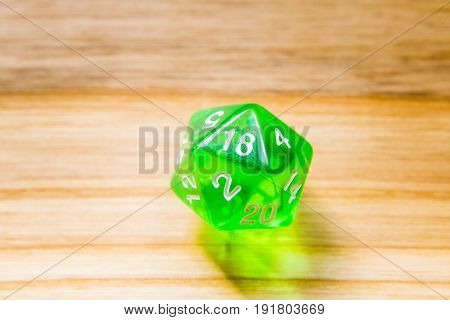A Translucent Green Twenty Sided Playing Dice On A Wooden Background With Number Eighteen On A Top